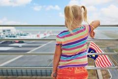 Junger Passagier betrachtet Flugzeuge im Flughafen stockbild