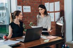 Junger persönlicher Assistent, der Pläne mit Chef in ihrem Büro bespricht stockbilder