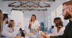 Junger positiver AfroamerikanerGeschäftsfrautrainer, der mit multiethnischen Angestellten an der Finanzseminarzeitlupe spricht stock video