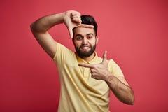 Junger positiver Mann im gelben T-Shirt, das Rahmen mit seinen Händen macht lizenzfreies stockbild