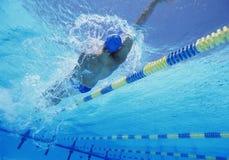 Junger professioneller männlicher Athlet, der Rückenschwimmen im Swimmingpool tut Lizenzfreies Stockfoto