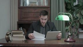 Junger Professor, der einen Videoanruf über die Tablette, zum des Papiers zu besprechen geschrieben von seinem Studenten hat stock video