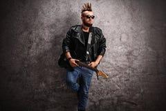 Junger Punkrocker, der eine E-Gitarre hält Stockbilder