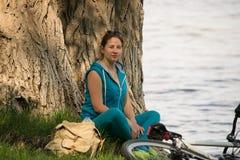 Junger Radfahrer auf dem Flussufer Stockfoto