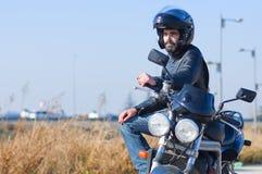 Junger Radfahrer auf seinem Motorrad und Sturzhelm stockfotografie