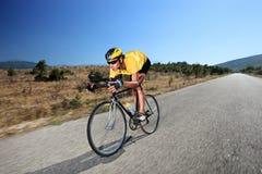 Junger Radfahrer, der ein Fahrrad auf eine geöffnete Straße reitet Lizenzfreies Stockfoto
