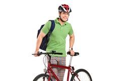 Junger Radfahrer, der nahe bei einem Fahrrad aufwirft Lizenzfreie Stockbilder