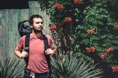 Junger Reisend-Mann mit dem Rucksack, der nahe alter hölzerner Wand mit Anlagen steht lizenzfreies stockbild