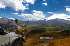Junger Reisend-Mann sitzt auf Auto und genießt Ansicht von Bergen im Sommer Elbrus-Region, Nord-Kaukasus, Russland Lizenzfreie Stockbilder