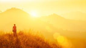 Junger Reisender, der am Berg bei Sonnenaufgang steht Reise, vacatio lizenzfreie stockfotos