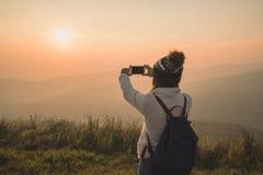 Junger Reisender, der Foto schönen Landschaftssonnenuntergang nimmt stockfotos