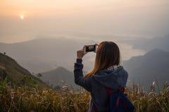 Junger Reisender, der Foto schönen Sonnenuntergang nimmt stockfotos