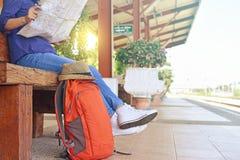 Junger Reisender, der mit Karte und Rucksack sitzt Lizenzfreie Stockfotografie