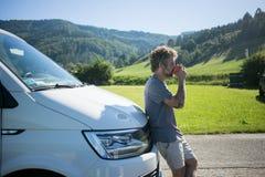 Junger Reisender genießt Tasse Kaffee nahe bei Packwagen lizenzfreie stockfotografie