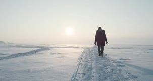 Junger Reisender läuft einen Blizzard bei schönem Sonnenuntergang durch Polare Expedition stock video footage