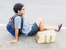 Junger reisender Mann sitzen auf der Straße Stockbilder