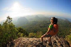 Junger Reisender mit Rucksack auf dem Bergspitzefelsen, Stelle beobachtend lizenzfreie stockfotos