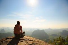 Junger Reisender mit Rucksack sitzen auf dem Bergspitzefelsen, Stelle beobachtend lizenzfreie stockbilder