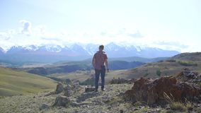 Junger Reisendmann mit dem Rucksack, der auf die Oberseite des Hügels mit Bergen und Hügeln herum sich entspannt 4 K stock footage