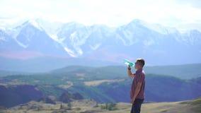 Junger Reisendmann trinkt Wasser und entspannt sich auf die Oberseite des Hügels mit Bergen und Hügeln herum 4 K stock video