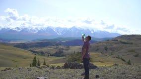 Junger Reisendmann trinkt Wasser und entspannt sich auf die Oberseite des Hügels mit Bergen und Hügeln herum 4 K stock footage