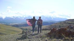Junger Reisendmann und -frau, die auf die Oberseite des Hügels mit Bergen und Hügeln herum sich entspannt Der Wandererstand auf d stock footage
