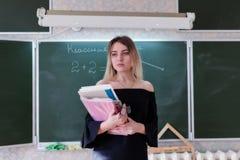 Junger reizend blonder Lehrer steht im Klassenzimmer mit einem Stapel O Lizenzfreie Stockfotografie