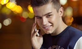Junger reizend Junge, der am Telefon spricht Stockbild