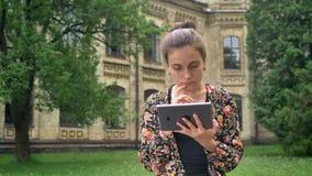 Junger reizend Student, der auf Tablette grast und im Park nahe Collegecampus, -konzentration und -vertrauen sitzt stock video