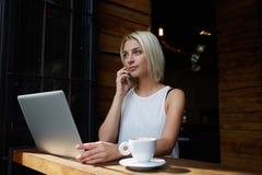 Junger reizend weiblicher Freiberufler, der mit Handy nennt, beim Sitzen im Café am Tisch mit Netzbuch, Stockfotografie