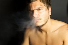 Junger reizvoller Mann, der eine Zigarette raucht Stockbilder