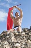 Junger reizvoller Mann mit einer roten Fahne Stockfotografie