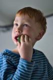 Junger roter behaarter Junge mit Gurke Lizenzfreie Stockfotos