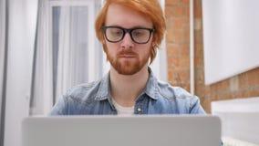Junger Rothaarige-Bart-Mann in der Glas-Funktion auf Laptop im Büro stock video