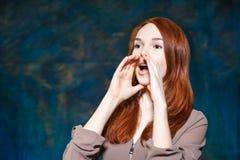 Junger Rothaarigemädchenschrei mit den Händen nähern sich Mund Lizenzfreies Stockfoto