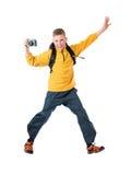 Junger rothaariger Junge in einer gelben Jacke und in einem Rucksack, die eine alte Kamera und ein Lächeln halten Lizenzfreie Stockfotos