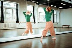 Junger rothaariger Tanzlehrer mit einem Haarbrötchen, das künstlerisch schaut lizenzfreie stockbilder