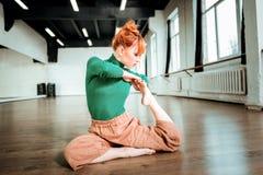 Junger rothaariger Yogalehrer mit dem Haarbrötchen, das beteiligt schaut lizenzfreies stockfoto