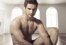 Junger ruhiger muskulöser Mann im Luxusplatz lizenzfreies stockfoto