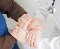 Junger süßer Doktor hält die Hand der alten Frau an Stockfotografie