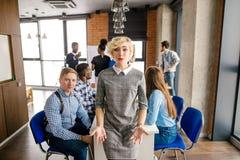 Junger schöner blonder Büroangestellter lädt ein, um an der Sitzung teilzunehmen Stockbilder