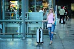 Junger schöner blonder Mädchenstellungsabschluß oben mit ihrem silbernen Koffer im Flughafen Stockbilder