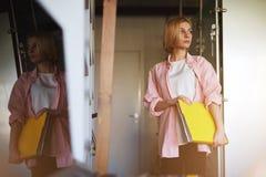 Junger schöner blonder Student, der in seiner modernen Wohnung mit einem großen Ordner mit Dokumenten steht Stockbilder