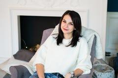 Junger schöner Brunette, der zu Hause auf Lehnsessel mit einem Kamin im Hintergrund stillsteht stockfotos