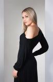 Junger schöner Brunette im schwarzen Kleid auf Weiß Lizenzfreies Stockfoto