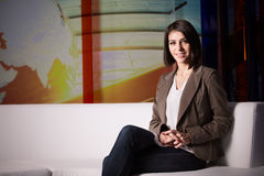 Junger schöner Brunettefernsehansager am Studio während der Livesendung Weiblicher Fernsehdirektor am Herausgeber im Studio Stockbild