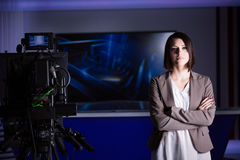 Junger schöner Brunettefernsehansager am Studio während der Livesendung Weiblicher Fernsehdirektor am Herausgeber im Studio Stockfotografie
