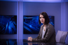Junger schöner Brunettefernsehansager am Studio während der Livesendung Weiblicher Fernsehdirektor am Herausgeber im Studio Lizenzfreie Stockfotos