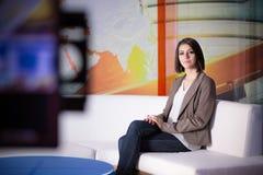 Junger schöner Brunettefernsehansager am Studio während der Livesendung Weiblicher Fernsehdirektor am Herausgeber im Studio Stockfoto