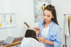 junger schöner Designer, der Stift in Gewebe setzt lizenzfreies stockfoto